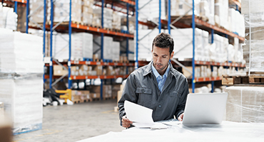 Man in warehouse on laptop